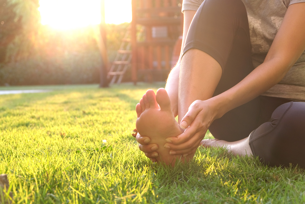 Woman with Plantar Fasciitis holding her foot outside.